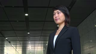 Portrait of happy beautiful Japanese female manager looking at camera. Young Asian businesswoman, confident girl, elegant woman smiling near office building. Career, success. Slow motion