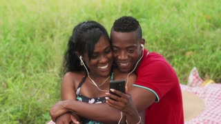 Couple Watching Video On Internet With Mobile Phone