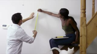 Do it yourself, diy, home improvement, interracial couple measuring wall to hang picture frame in living room at home