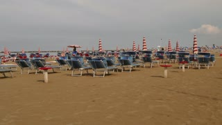 Empty sandy beach with sunbeds and umbrellas after rain storm. People on holiday in Italy, tourists on summer vacation. Italian coast in Igea Marina on Adriatic Sea. Famous tourist destination
