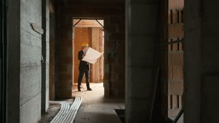 Engineer at work in construction site, standing in new apartment building and looking at blueprints and plans. Sequence