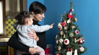 Family With Happy Mom And Child Looking At Christmas Tree