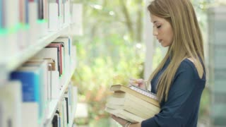 Female college student taking book from shelf in library and looking at camera. School, education, girl, woman