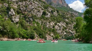 Gorges du Verdon (Verdon Gorge) near Lac de Sainte-Croix in southern France. View of French landscape with canyon, mountain, crystal clear waters river. People having fun on boats, kayaks, canoes