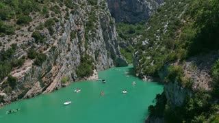Gorges du Verdon (Verdon Gorge) near Lac de Sainte-Croix in southern France. View of French natural landscape with canyon, mountain, crystal clear water river. People having fun on boat, kayak, canoe