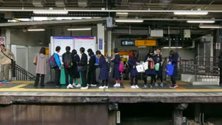 Group of school children and friends waiting for the local train on the platform at the Tofukuji JR railway station. Kyoto, Japan, Asia