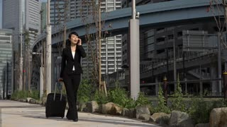 Happy beautiful Japanese female manager speaking on cell phone. Asian businesswoman, confident girl, busy woman talking with mobile telephone and walking with luggage during business trip. Slow motion