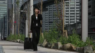 Happy beautiful Japanese female manager speaking on cell phone. Asian businesswoman, successful girl, busy woman talking with smartphone and walking with luggage during business travel
