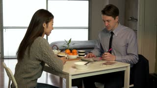 Happy Businessman And Woman Having Breakfast Talking At Home