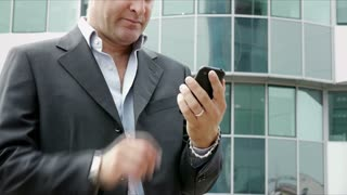 Happy businessman with mobile telephone, smartphone, visiting web site, browsing the internet, sending email