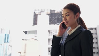 Happy Japanese Asian Businesswoman Talking On Phone Near Office Buildings