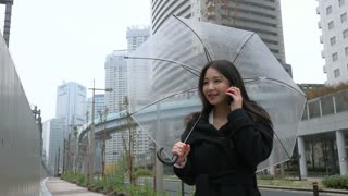 Happy Japanese female manager speaking on cell phone. Asian businesswoman, confident girl, busy woman talking with smartphone, mobile telephone near office buildings with umbrella in the rain
