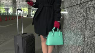 Happy Japanese female manager speaking on cell phone during business trip. Asian businesswoman, confident girl, busy woman talking with smartphone, mobile telephone near office building in winter