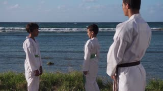 Happy Karate Sport Instructor Watching Young Boys Fighting And Training