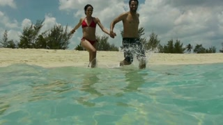 Happy man and woman having fun,  jumping into the water on tropical beach near the sea during vacation