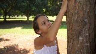 Happy school girl hugging tree in park, ecology, people