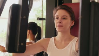 Happy young people, fun, leisure, lifestyle, fitness, sport and exercising. Beautiful caucasian young woman working out, pretty girl training with equipment in gym. Portrait looking at camera