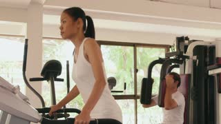 Happy young people, fun, leisure, lifestyle, fitness, sport and workout, man and woman training in gym. Portrait of asian girl looking at camera when jogging on treadmill