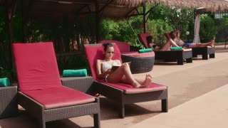 Happy young people, fun, leisure, lifestyle, vacations and relax near resort swimming pool, beautiful asian woman drinking cocktail and reading book in hotel, with waitress serving drin