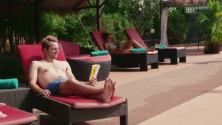 Happy young people, fun, leisure, travel, vacation and relax near resort swimming pool, man and woman drinking cocktail, talking and reading book in hotel. Portrait smiling at camera