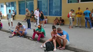 Havana, Cuba. Cuban people using mobile telephone, cell phone, smartphone and ipad digital tablet for internet, social media, network and email. Wireless wi-fi technology in Calle Obispo