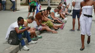 Havana, Cuba. Cuban youth using mobile telephones, cell phones, smartphones and ipad digital tablet for internet, social media, network and email. Wireless wifi technology in Calle Obispo