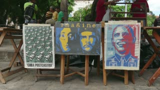 Havana, Cuba. Tourist market with shop, fair with stall selling souvenirs, books, posters with Che Guevara, president Barack Obama and John Lennon for tourists. People shopping