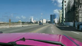 Havana, Cuba. View of Malecon promenade and Caribbean sea from windshield of a 1959 Cadillac, pink classic vintage car, old taxi, cab in Cuban city traffic. Travel, transportation, transport, tourism