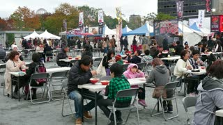 Hiroshima, Japan, Asia. Japanese people, families and tourists enjoy their holidays eating traditional street food at city fair