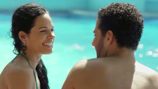 Honeymoon, happy young newlyweds smiling and relaxing near hotel pool. Man, woman in resort, holidays, vacation, relax, fun