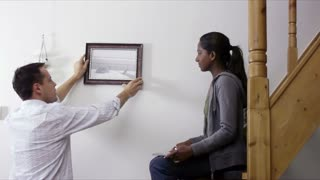 Interracial couple hanging pictures to the wall at home, home improvement and decoration, diy