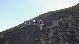 Italy, Italia, Sicily, Sicilia travel, people and sport. Hikers, trekkers climbing slope of Stromboli volcano, Aeolian Islands, Eolie. Eruption and lava in crater. Sequence