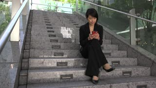 Japanese female manager texting, sitting on stairs. Asian businesswoman, girl, woman at work, using mobile phone, telephone, smartphone for email, internet