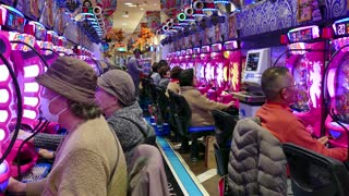 Japanese people playing pachinko, lottery, arcade game, videogame, video games, gambling, slot machines in Asian casino. Kyoto, Japan, Asia