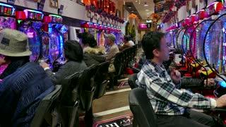 Japanese people playing pachinko, lottery, arcade game, videogame, video games, gambling, slot machines in Asian casino. Kyoto, Japan, Asia