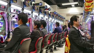 Japanese people playing pachinko, lottery, arcade game, videogame, video games, gambling, slot machines in Asian casino. Tokyo, Japan, Asia