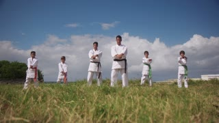 Karate School With Trainers And Young Boys Showing Fighting Techniques