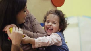 Kindergarten, teacher playing and laughing with little young girl