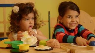 Little children and educator playing in kindergarten