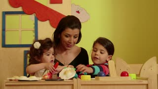Little children, babies, playing in kindergarten, school. Woman at work as educator in preschool having fun with cute little girls. Recreation and education