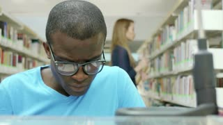 Male black college student reading book in school library, with caucasian woman taking book from shelves in background. Dolly shot