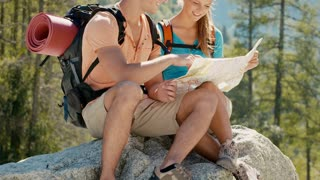 Man and woman during leisure activity on holidays, young people hiking and trekking on mountains, talking and looking at map