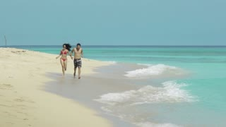 Man and woman, husband and wife, couple, just married young adults playing and smiling on a tropical beach in Cuba, Caribeban sea. Honeymoon, travel, holidays, sea