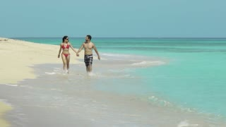 Man and woman, husband and wife, couple of young newlyweds walking on the beach in Cuba. Honeymoon, travel, holidays, sea