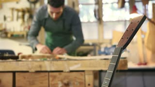 Man at work as craftsman in workshop with guitar and musical instrument, smoothing guitar body