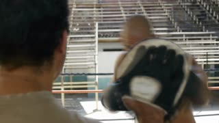 Man practicing with trainer in boxing ring athlete boxe sport