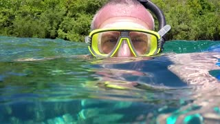 Man swimming underwater in sea, apnea free diving, snorkeling near coral reef, holding GoPro video camera. Leisure, summer fun, recreation, holidays, water sport in Palau, Micronesia, Pacific Ocean