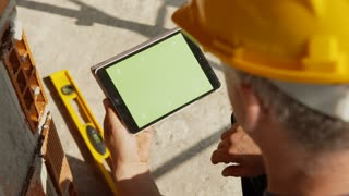 Manual worker, engineer, architect at work in construction site using ipad digital tablet with green screen