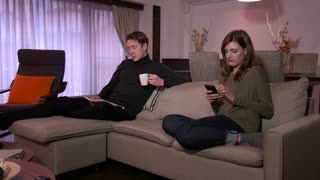 Married Couple Husband And Wife Relaxing On Couch At Home