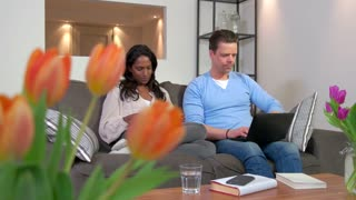 Married interracial couple using ipad digital tablet and laptop computer, people relaxing on couch at home. Wireless technology for internet, email, lifestyle, relaxation, fun with husband and wife